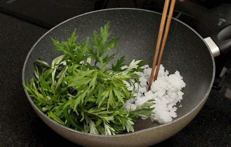 Sao nóng ngải cứu với muối hạt rồi dùng để chườm lên lưng giúp giảm đau nhức